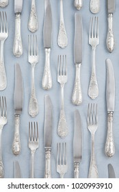 Silverware knives and forks on a blue tablecloth background. Table setting. Pattern