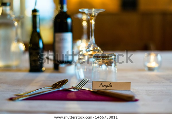 Silverware, napkin, glassware and candles sit on a white tablecloth at a dinner with a place card that reads Family in Italian.