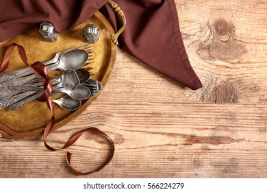 Silverware with napkin on wooden background