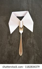 Silverware as a tie under a paper collar against a black background - concept with cutlery as a tie and dark background