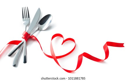 Silverware tied up with red ribbon in heart shape isolated on white background. Concept Valentines Day dinner