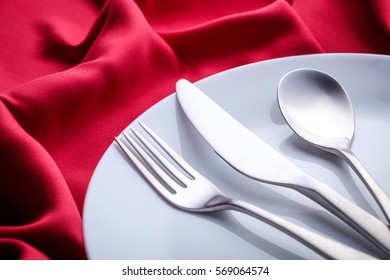 Silverware and white ceramic plate close up on red satin cloth.