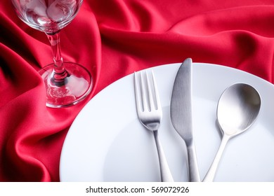 Silverware white ceramic plate and wine glass box close up on red satin cloth.