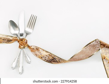 Silverware Wrapped with Holiday Gold Ribbon