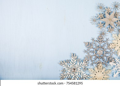 Silvery snowflakes on a blue wooden background. Christmas decor.