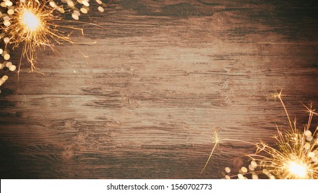 Silvester background banner - frame made of snow with snowflakes, sparklers and lights on rustic wooden texture, top view with space for text