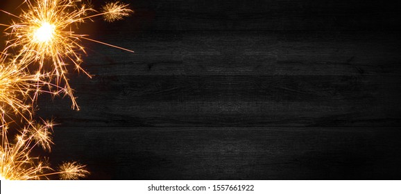 Silvester background - sparklers and lights on rustic dark black wooden texture, top view with space for text
