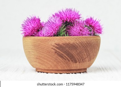Silybum marianum (milk thistle) flowers in a wooden bowl.One of the most common uses of milk thistle is to treat liver problems.Alternative medicine concept on a white wooden table (selective focus).