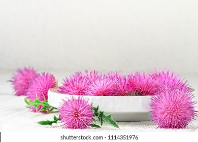 Silybum marianum (milk thistle) herb in a bowl.One of the most common uses of milk thistle is to treat liver problems.Alternative medicine concept on a white wooden table (selective focus).