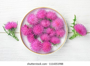 Silybum marianum (milk thistle) herb in a bowl.One of the most common uses of milk thistle is to treat liver problems.Alternative medicine concept on a white wooden table, top view (selective focus).