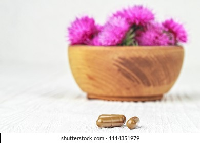 Silybum marianum (milk thistle) pills and flowers on a white wooden table (selective focus).One of the most common uses of milk thistle is to treat liver problems