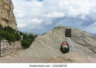 """Simeiz, Crimea, Russia - September 09, 2018: Stone with a commemorative plaque in the Russian language """"in loving memory of Lina Gavriel and Pavel Akaluka - Komsomol underground executed by the Nazis"""""""