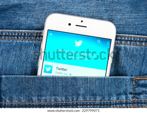 SIMFEROPOL, RUSSIA - NOVEMBER 11, 2014: Silver Apple iphone 6 in jeans pocket displaying Twitter application. Twitter is an online social networking service that send and read messages