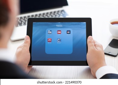 Simferopol, Russia - September 13, 2014: iPad in the hands of a businessman with popular news applications on the screen. iPad is created and developed by the Apple inc.