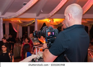 Simi Valley, CA - October 5, 2015: A wedding videographer taking video  of a wedding party at The Vineyards.   The Vineyards in Simi Valley. The Vineyards is a popular destination for weddings.