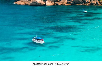 Similan, Thailand - Feb 2017: Speed boats off the Similan Islands amid bright blue clear water and coral reefs at the bottom. Snow-white pleasure motor yachts and tourists having a rest. Chic holiday