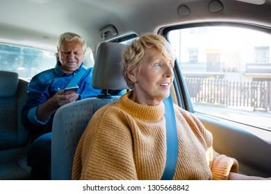 Similing senior female driver talking with male passenger. Senior man holding mobile phone in hand.