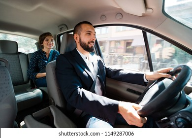 Similing taxi driver talking with female passenger.