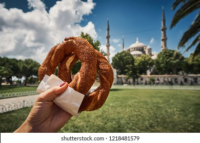 Simit Turkish bagel traditional culture street food bakery bread roll with sesame seeds pretzel snack launch breakfast meal on Blue Mosque Sultanahmet famous travel sight background Istanbul Turkey.