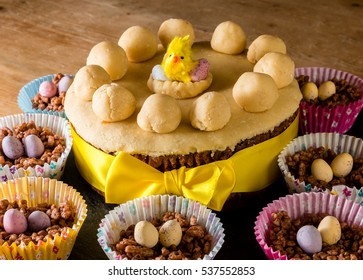 Simnel cake at Easter.  Covered in yellow marzipan with a chick toy on top.  The simnel cake has a yellow ribbon and is surrounded by chocolate crispy cakes with mini chocolate eggs on top