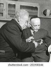 Simon Trampatter, 83-year-old Dutch Jew cuts star off the coat of his friend, Joseph Keller. Both men had been residents of Kerkrade, Netherlands, when the World War 2 began in 1939. Jan. 17, 1945.