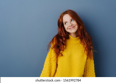 Simpering young woman with a coy smile looking aside with a smile as she flirts over a blue studio background with copy space