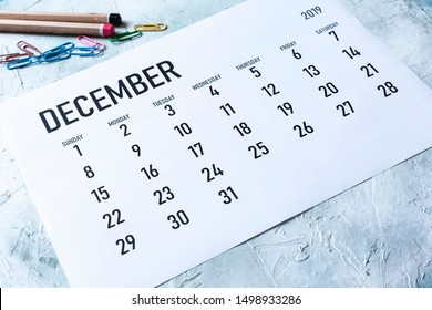 Simple 2019 December monthly calendar on table with office supplies