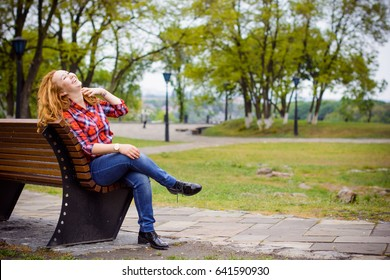 Simple american girl from next door in a plaid shirt walk in central park. Smiling and laughing have fun time