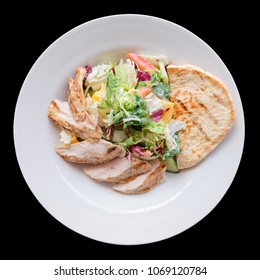 Simple appetizer with grilled chicken fillet on wooden table shot from above, isolated on black background