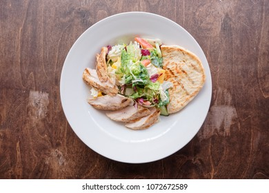 Simple appetizer with grilled chicken fillet on wooden table shot from above