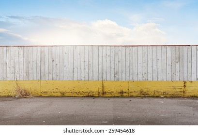 Simple artistic background with wooden fence and blue sky