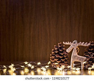 Simple background with a rustic wooden moose ornament and christmas lights