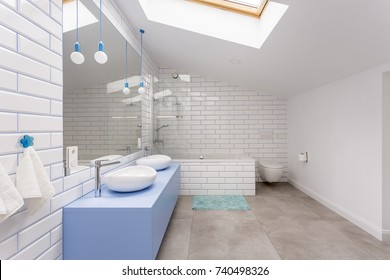 Simple bathroom in the attic with blue washbasin cabinet, toilet and bathtub against white brick wall