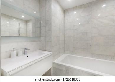 El interior del cuarto de baño es sencillo, con bañera, lavabo y paredes de mármol