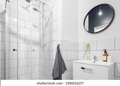 Simple bathroom with small shower round mirror and classic, white tiles
