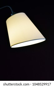 Simple, but beautiful lampshade with light on. Isolated on black background. Vertical image with room for text.