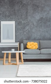 Simple beautiful living room with gray wall, comfortable couch, white and wooden coffee table, console table, poster, rug and yellow decorative pillow