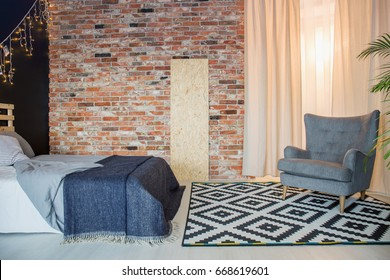 Simple bed and elegant stylish chair in contemporary fashionable room with brick wall