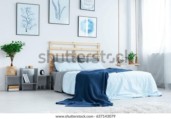 寝室とダブルベッド、青い寝具、ポスター、窓