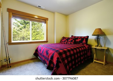 Simple bedroom with flannel bedding in cabin style house.
