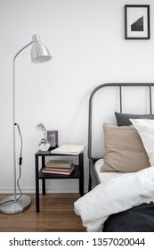 Simple bedroom interior with bed, lamp and nightstand
