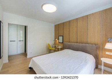 Simple bedroom interior with double bed, nightstand, small glass table , white bedding and wardrobe