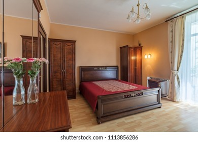 Simple bedroom with window and cupboard in daylight