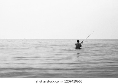 Simple black and white panorama divided in half photo of a lonely fisherman on Koh Lanta island, Thailand, fishing on the horizon with his spinning line with half of his body submerged in water