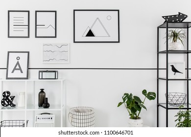 Simple black and white posters hanging on white wall in Nordic style living room interior