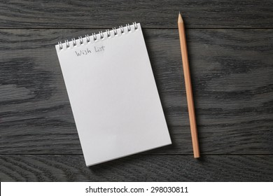 simple blank notepad with phrase wish list on rustic wood table, background
