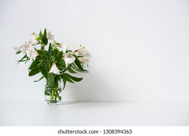 Simple bouquet with Alstroemeria flowers and empty white wall