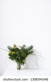 Simple bouquet with green leaves and mimosa flowers and empty white wall