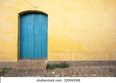 Simple brightly painted blue door in a smooth yellow ochre stucco wall on a cobblestone street in Trinidad, Cuba