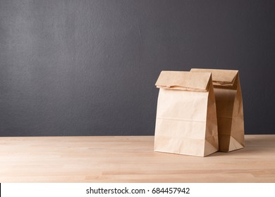 simple brown paper bag for lunch or food on wooden table with copy space